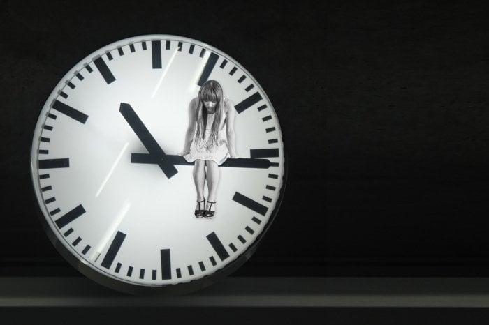 時計の長針に座る女性